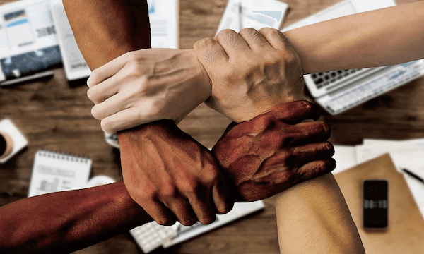 Four hands grabbing the other's wrists, teamwork